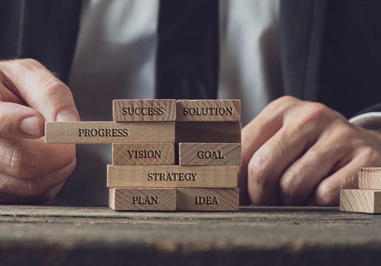 Businessman stacking wooden pegs with words of business strategy, vision and development on them in a conceptual image.